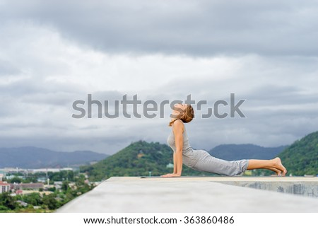Yoga on rooftop. Happy young woman stretching on roof with city and mountains view.