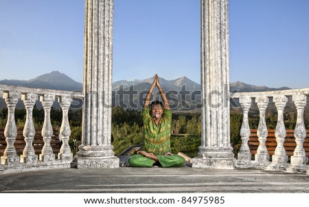 Yoga padmasana lotus pose is done by funny Indian man in green cloth between stone columns at mountain background - stock photo