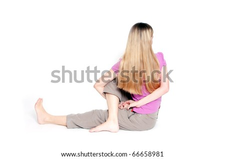 "Yoga pose called ""sitting half spinal twist"" by young woman. - stock photo"
