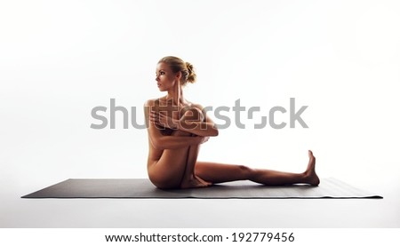 Yoga pose demonstrated by beautiful woman. Nude woman sitting on exercise mat performing yoga over white background. - stock photo