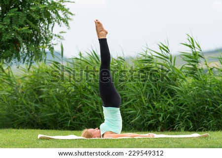 Yoga Pose in the park Suppor ted Shoulderstand - stock photo