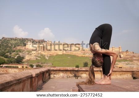 Yoga pose Standing forward fold or Uttanasana  at Amber fort, Jaipur, India - stock photo