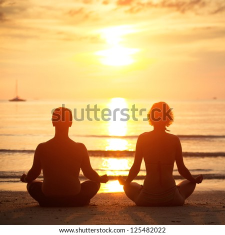Yoga practice: a young couple sitting on the beach of the sea in the lotus position at sunset. - stock photo