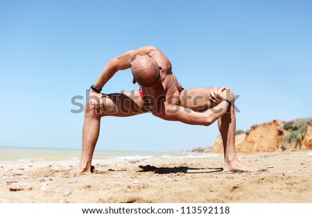 Yoga practice. Man doing strong spinal twist yoga pose at the sand beach