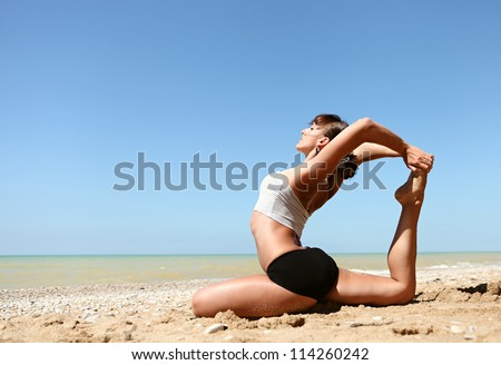 Yoga practice. Young girl doing king pigeon yoga pose on the beach - stock photo