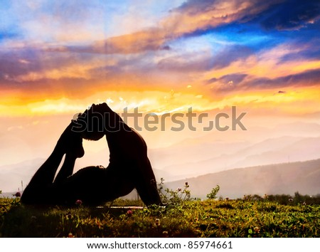Yoga Raja Kapotasana backward bending pose by Man in silhouette on the grass outdoors at mountains and cloudy sky with sunrays background - stock photo
