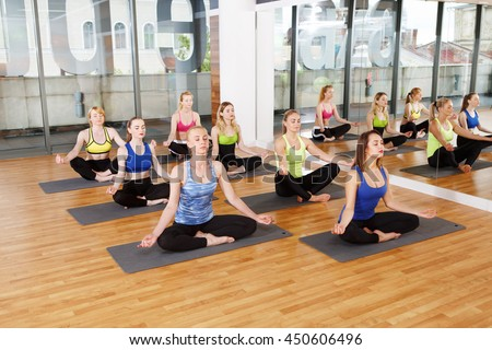 Yoga relaxation. Group of young women in sport class making exercises. Girls do meditation pose for relax after training. Healthy lifestyle in fitness club - stock photo