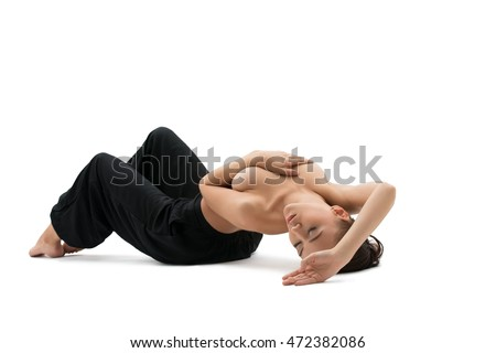 Yoga. Relaxed young woman posing topless in studio
