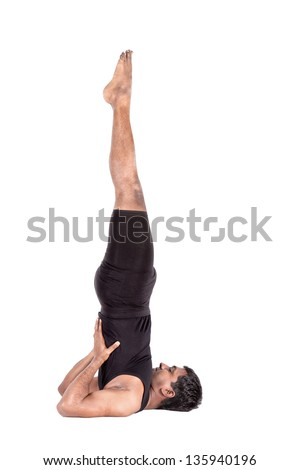 Yoga salamba sarvangasana shoulder stand pose by Indian man in black costume isolated at white background. Free space for text - stock photo
