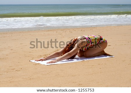 yoga stretches on the beach - stock photo