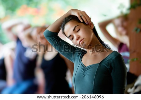 Yoga stretching neck. Public yoga classes. Exercise Stretching the neck. Girl with eyes closed stretches neck with his right hand. May 2014. Moscow, Russia - stock photo
