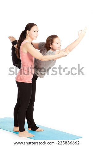 Yoga teacher provides assistance in training - stock photo