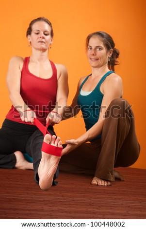 Yoga trainer helps student stretch with elastic band - stock photo
