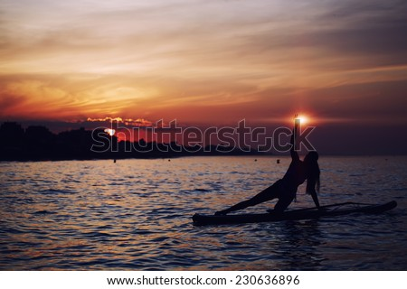 Yoga training in harmony with nature, silhouette of yoga woman holding light in the hand, spiritual concept, paddle board yoga performed by beautiful woman with bright sunset on background - stock photo