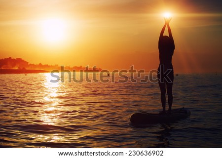 Yoga training in harmony with nature, silhouette of yoga woman holding lights in the hands, spiritual concept, stand up paddle board yoga performed by beautiful woman with bright sunset on background - stock photo