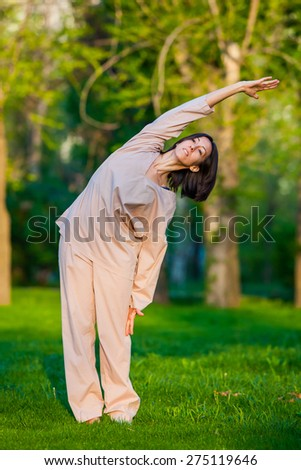 Yoga utthita trikonasana triangle pose by woman in white costume on green grass in the park around pine trees