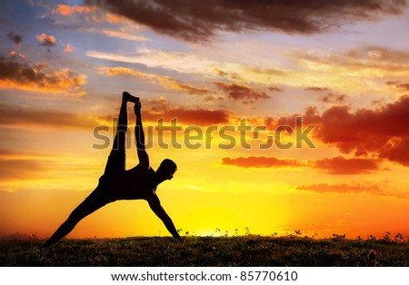 Yoga Vasisthasana plank balancing pose by Man in silhouette with dramatic sunset sky background. Free space for text - stock photo