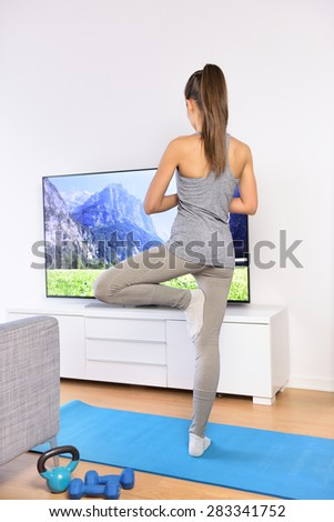 Yoga video class - woman training at home in living room in front of the television following a fitness program or watching her favorite TV show.