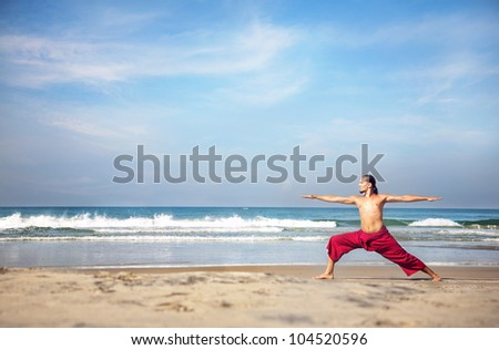 Yoga virabhadrasana II warrior pose by fit man with long hair in red trousers on the beach at ocean background - stock photo