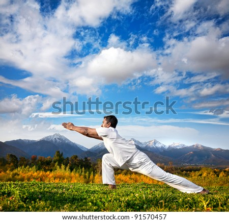 Yoga virabhadrasana warrior pose by Indian Man in white cloth in the morning at mountain background - stock photo
