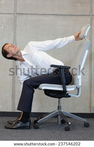 yoga with arm chair in office - business man exercising - stock photo