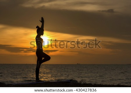 Yoga with young girl in silhouette