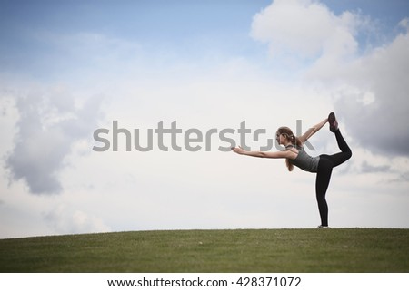 Yoga woman in park. Woman training in urban park at sunset intentional sun glare. Photo of sporty woman doing yoga with nature.
