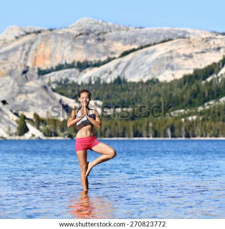 Yoga woman meditating in nature meditation retreat. Young female adult relaxing standing in tree pose in the middle of a serene lake surrounded by mountains and forest for a relaxation concept. - stock photo