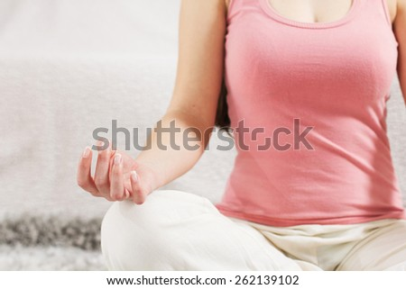 Yoga Woman Meditating Relaxing at home.Healthy Lifestyle in Lotus Posture .Unrecognizable caucasian female practicing on the floor. - stock photo
