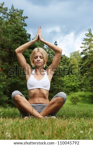 yoga woman on green park. Beautiful young woman doing yoga exercise. Outdoor sport