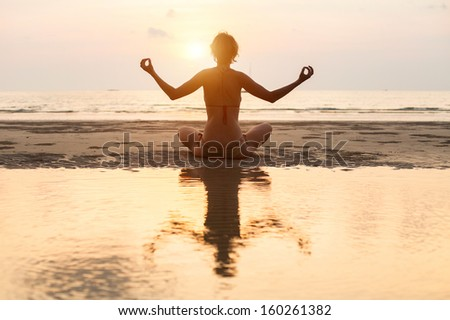 Yoga woman sitting in lotus pose on the beach during sunset (with reflection in water) - stock photo