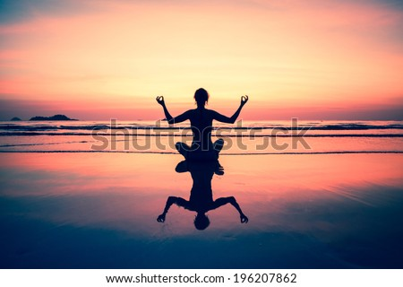 Yoga woman sitting on sea coast at sunset, picture-in-surreal colours. - stock photo