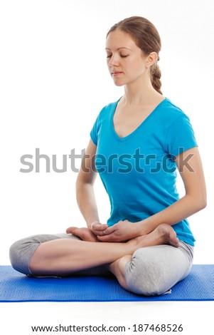 Yoga - young beautiful woman yoga instructor doing Lotus Position (padmasana with bhairava mudra) asana exercise - cross-legged sitting asana for meditation - isolated on white background - stock photo