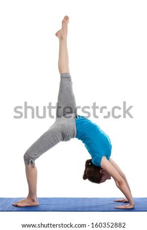 Yoga - young beautiful woman yoga instructor doing Wheel Pose with one leg lifted straight up (Eka Pada Chakrasana) exercise isolated on white background - stock photo