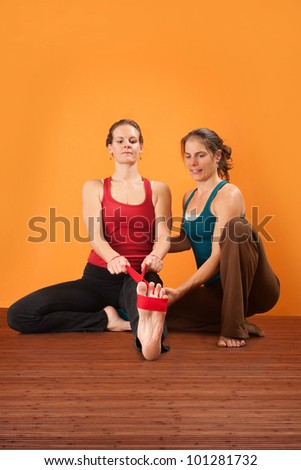 Yogasana instructor helps student stretch her leg - stock photo
