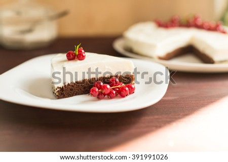 yoghurt cheesecake with fresh red currants on wooden table - stock photo