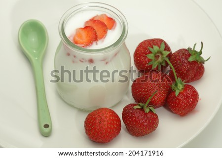 Yoghurt pot and fresh raspberries  isolated on white background