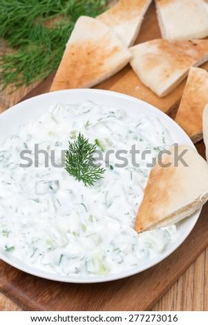 yoghurt sauce tzatziki with herbs, cucumber and garlic and pita bread, vertical - stock photo