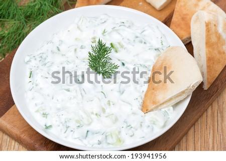 yoghurt sauce tzatziki with herbs, cucumber and garlic, top view, close-up - stock photo