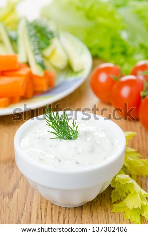 yoghurt sauce with herbs to assorted fresh vegetables on a wooden table close-up