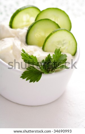 yoghurt with cucumber. Fresh dip of famous Greek taziki with cucumber - stock photo