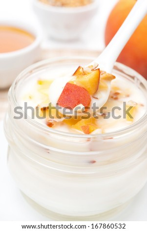 yoghurt with honey, peaches, nuts in a spoon, close-up - stock photo