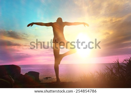Yogi meditating at sunset on the sea - stock photo