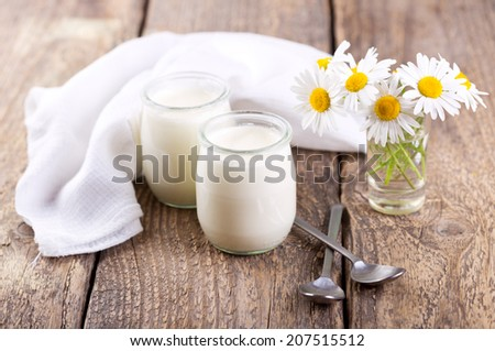 yogurt in a glass jars on wooden table - stock photo