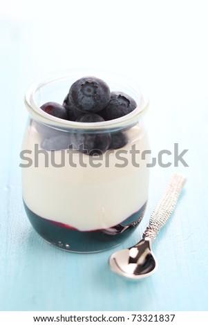 Yogurt in glass jar with jam and fresh blueberry - stock photo