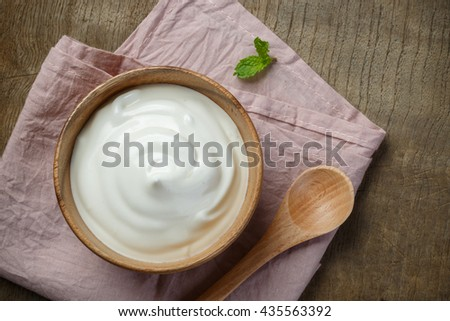Yogurt in wooden bowl on wooden background with pink cotton and wooden spoon. plain yoghurt. yogurt. yoghurt. - stock photo