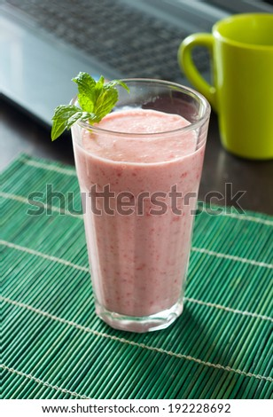 Yogurt strawberry cocktail in the background laptop computer - stock photo