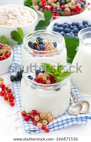 yogurt with berries and breakfast foods, vertical - stock photo
