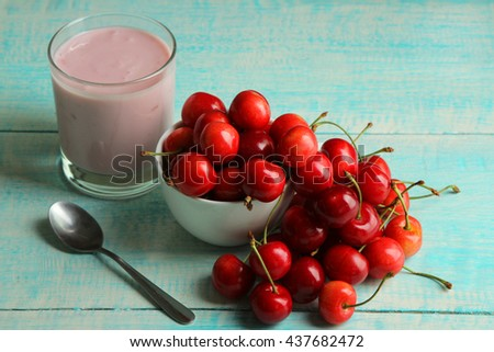 yogurt with cherry flavor in a glass on wooden background with scattered cherry blossoms near the iron spoon - stock photo