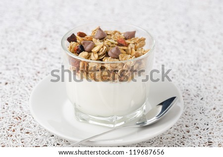 Yogurt with muesli and chocolate drops in a glass beaker of portion